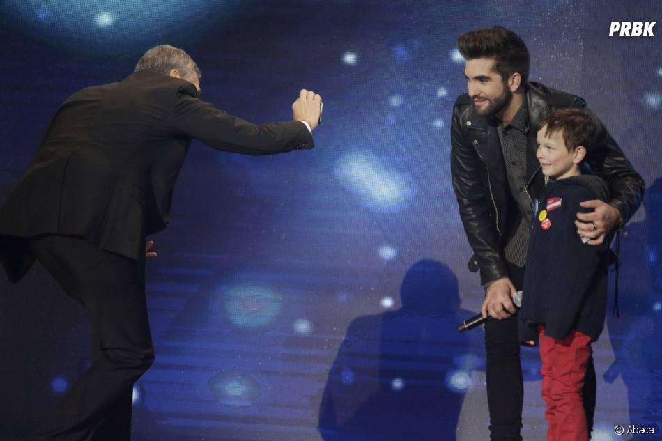 Kendji Girac pose avec un jeune fan à la soirée du Téléthon sur France 2 le 5 décembre 2015