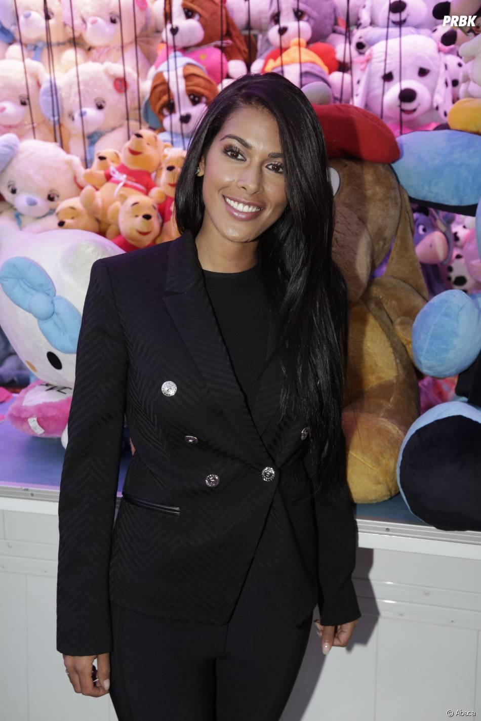 Ayem Nour souriante lors de la soirée d'ouverture de la Foire du Trône à Paris, le 27 mars 2015