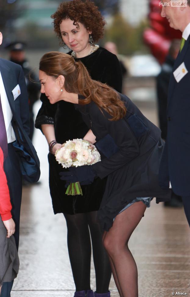 Kate Middleton dévoile un bout de cuisse à cause du vent, à Londres le 19 novembre 2013