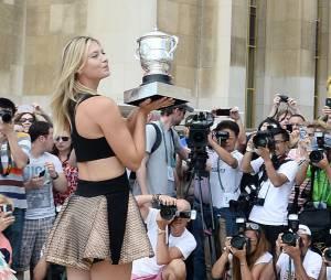 Maria Sharapova en robe courte pour présenter son trophée après sa victoire en finale de Roland Garros 2014