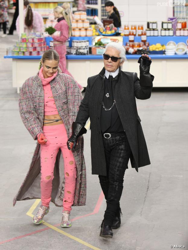 """Cara Delevinge au bras de Karl Lagerfeld pour le défilé Chanel dans le """"Shopping Center"""" du Grand Palais, le 4 mars 2014 à Paris"""