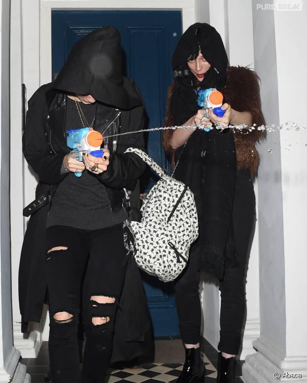 Cara Delevingne et sa petite-amie St Vincent arrosent les paparazzi, le 18 décembre 2015 à Londres