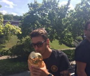 Mesut Özil embrasse la Coupe du Monde qu'il a remporté avec l'équipe allemande, le 6 juillet dernier