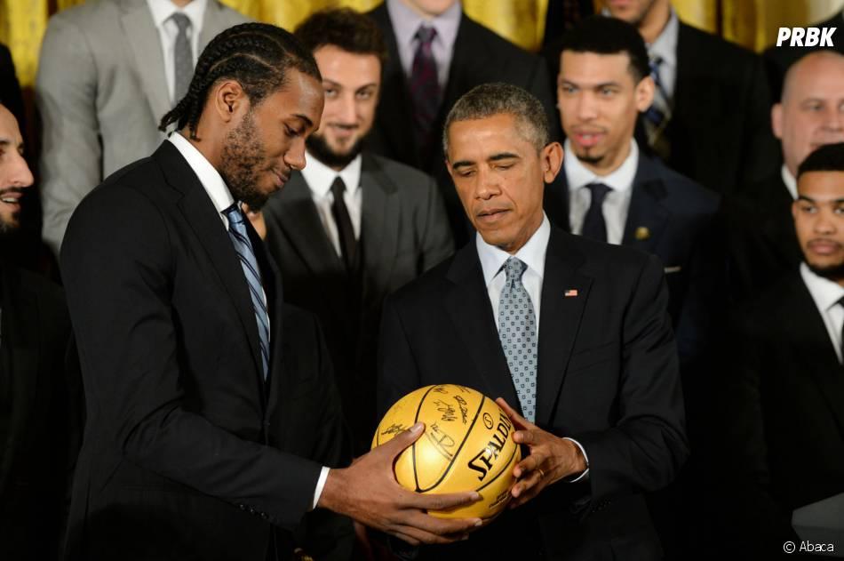Barack Obama reçoit un ballon de basket signé par les joueurs des San Antonio Spurs, le 12 janvier 2015 à la Maison Blanche (Etats-Unis)
